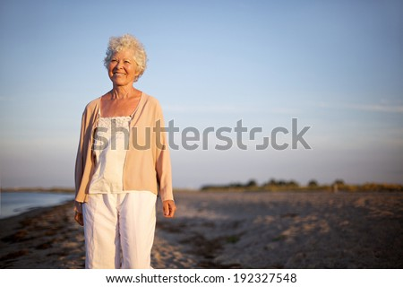 Portrait of happy mature woman standing at the beach looking at camera. Smiling old lady standing alone on the beach. Relaxed senior caucasian woman outdoors - stock photo