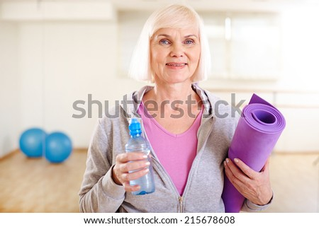 Portrait of happy mature woman with bottle of water and rolled mat - stock photo
