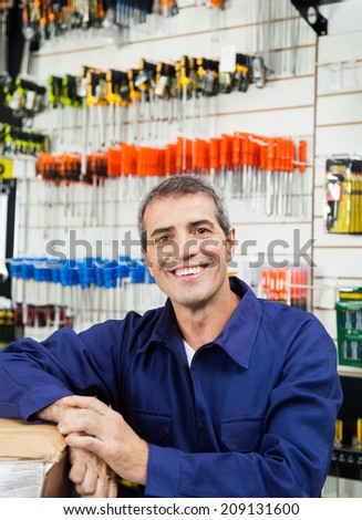 Portrait of happy mature worker in hardware shop - stock photo