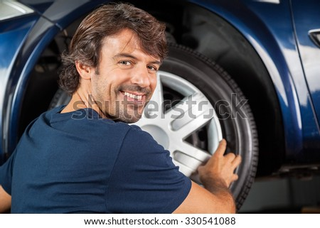 Portrait of happy mechanic fixing hubcap to car tire at garage - stock photo