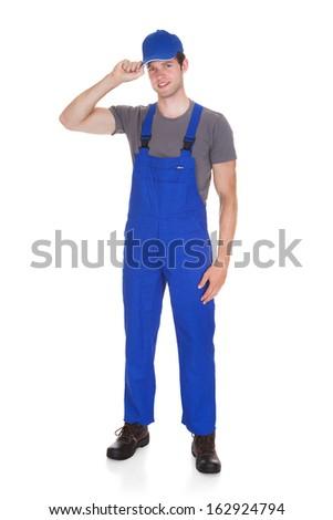 Portrait Of Happy Mechanic Holding Cap On White Background - stock photo