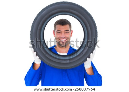 Portrait of happy mechanic looking through tire on white background