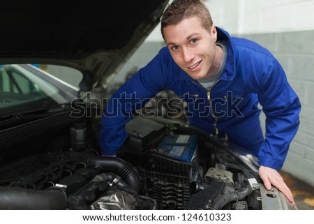 Portrait of happy mechanic repairing under car hood
