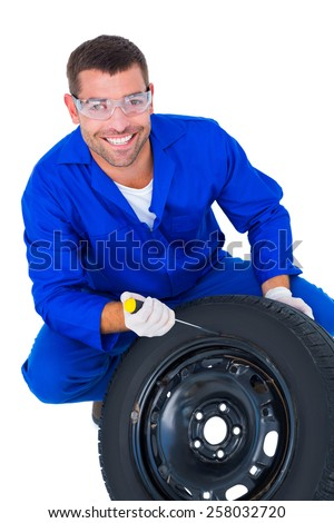 Portrait of happy mechanic working on tire over white background