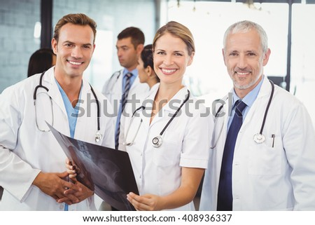 Portrait of happy medical team holding a x report in hospital