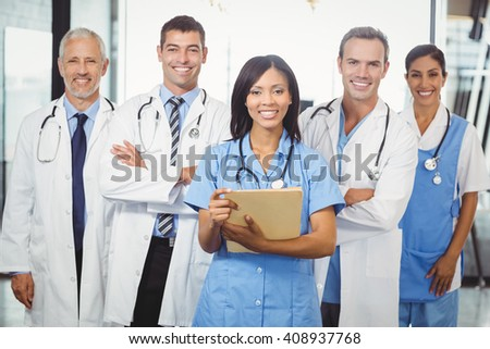 Portrait of happy medical team standing together in hospital - stock photo