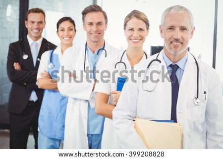 Portrait of happy medical team standing with arms crossed in hospital