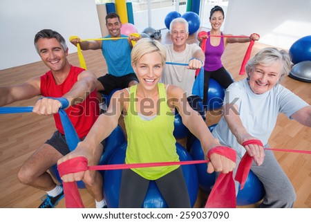 Portrait of happy men and women on fitness balls exercising with resistance bands in gym class - stock photo