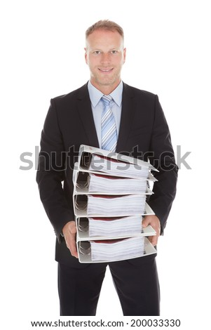 Portrait of happy mid adult businessman carrying stack of binders over white background - stock photo