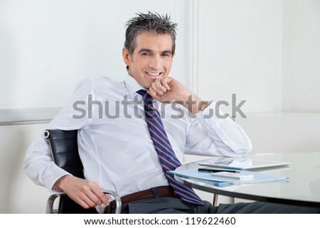 Portrait of happy mid adult businessman with digital tablet relaxing at desk in office - stock photo