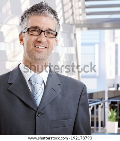 Portrait of happy mid adult caucasian male business advisor. Wearing suit and glasses, looking at camera, smiling. Copyspace. - stock photo