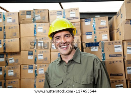 Portrait of happy mid adult foreman at warehouse - stock photo