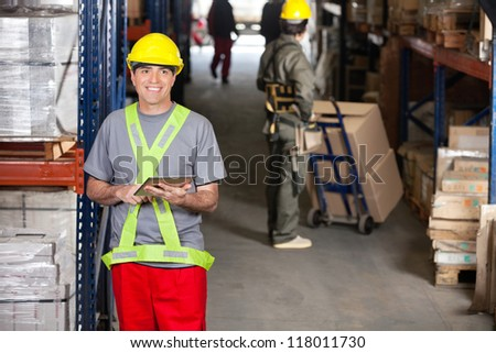 Portrait of happy mid adult foreman with digital tablet and coworker pushing handtruck at warehouse - stock photo