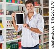 Portrait of happy mid adult man showing digital tablet in supermarket - stock photo