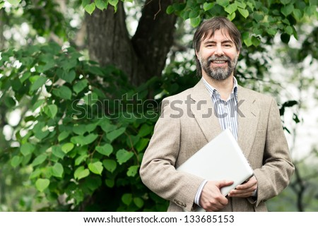 Portrait of happy middle-aged businessman holding notebook and smiling, outdoors