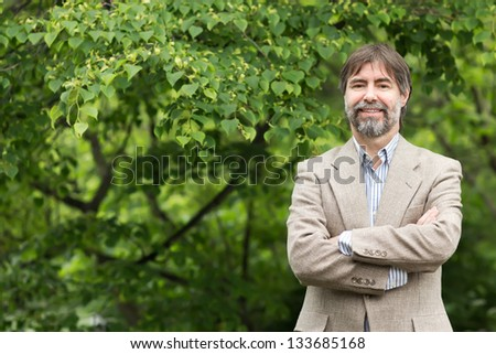 Portrait of happy middle-aged businessman looking at camera and smiling, outdoors. -copyspace - stock photo