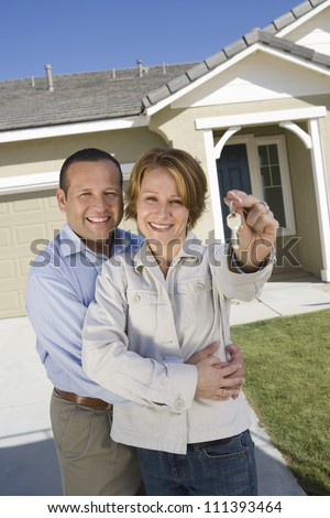 Portrait of happy middle aged couple holding key in front of new house