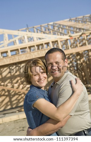 Portrait of happy middle aged couple in front of house under construction