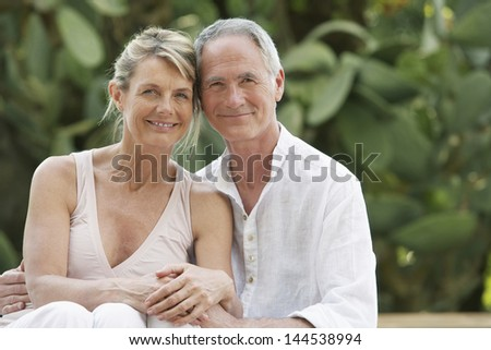Portrait of happy middle aged couple relaxing in garden - stock photo