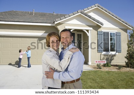 Portrait of happy middle aged couple with daughters in front of new house - stock photo