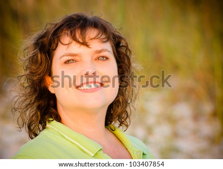 Portrait of happy middle-aged woman at beach with sand dunes in background