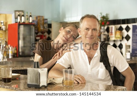 Portrait of happy middle aged woman relaxing on man's shoulder in bar - stock photo