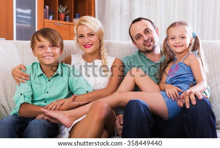 Portrait of happy middle class caucasian family at home interior. Focus on boy - stock photo
