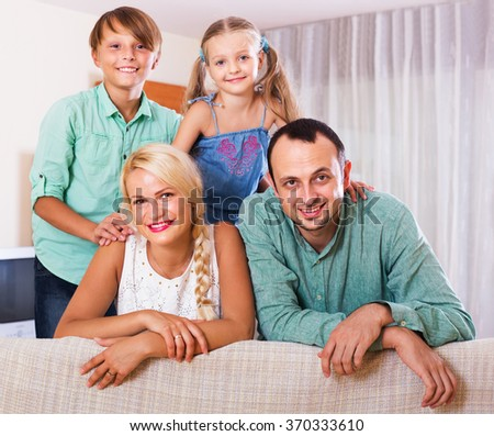 Portrait of happy middle class caucasian family with two children at home. Focus on woman - stock photo
