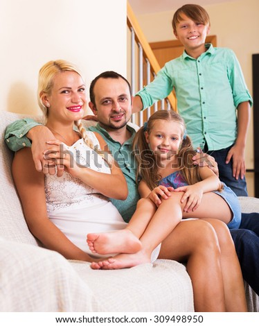 Portrait of happy middle class family with two children at home. Focus on woman - stock photo