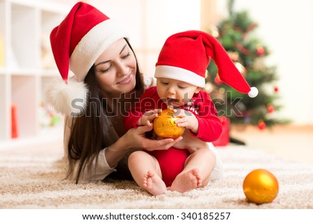 Portrait of happy mother and adorable baby holding bauble against domestic festive backdrop with Christmas tree