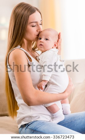 Portrait of happy mother and baby at home