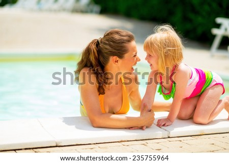 Portrait of happy mother and baby girl at poolside - stock photo