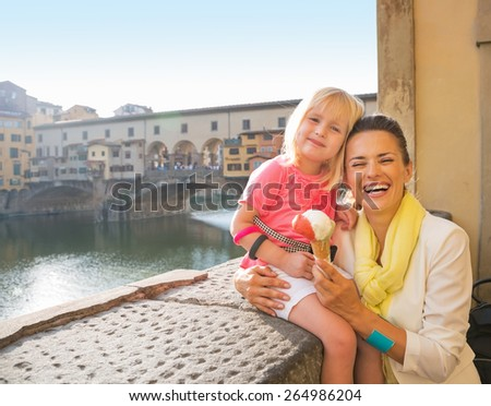 Portrait of happy mother and baby girl eating ice cream near ponte vecchio in florence, italy - stock photo