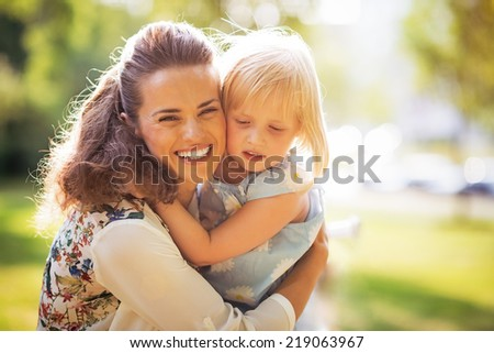 Portrait of happy mother and baby girl hugging