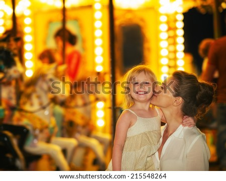 Portrait of happy mother and baby girl in front of carousel - stock photo