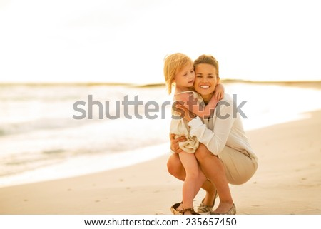 Portrait of happy mother and baby girl on beach at the evening - stock photo