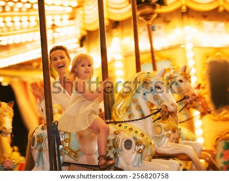 Portrait of happy mother and baby girl riding on carousel - stock photo