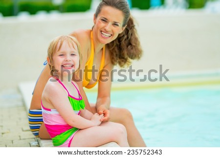 Portrait of happy mother and baby girl sitting at poolside
