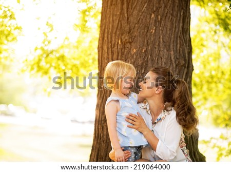 Portrait of happy mother and baby girl standing near tree - stock photo