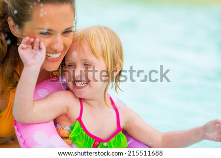 Portrait of happy mother and baby girl swimming in pool - stock photo