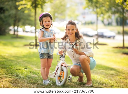 Portrait of happy mother and baby girl with bicycle - stock photo