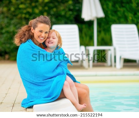 Portrait of happy mother and baby girl wrapped in towel sitting near swimming pool - stock photo