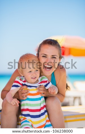 Portrait of happy mother and baby on beach - stock photo