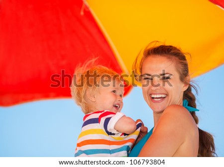 Portrait of happy mother and baby on beach under umbrella - stock photo