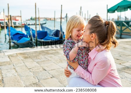 Portrait of happy mother and baby on grand canal embankment in venice, italy - stock photo