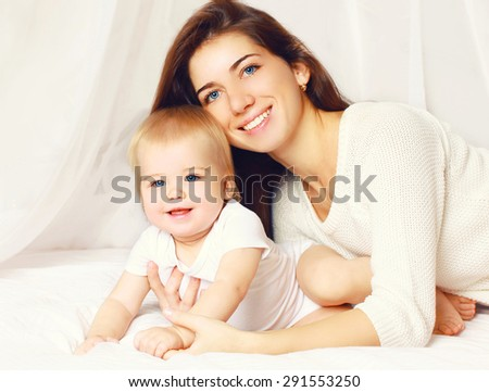 Portrait of happy mother and baby playing and having fun together on the bed at home - stock photo