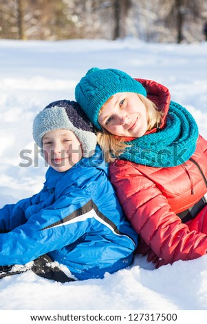 Portrait of happy mother and child  in snow on a cold winter day - stock photo