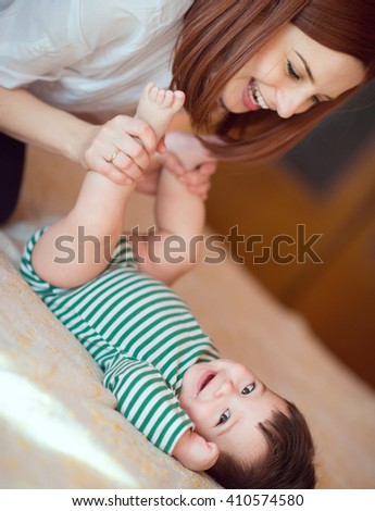 Portrait of happy mother and child laughing and playing