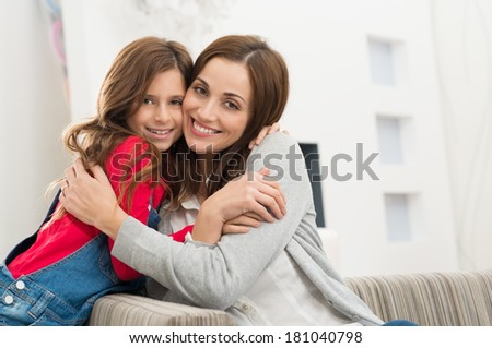 Portrait Of Happy Mother And Daughter Embracing Looking At Camera - stock photo