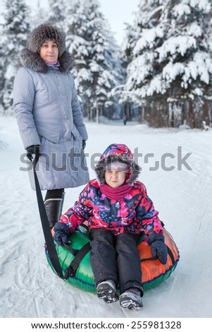 Portrait of happy mother and daughter going riding with tube at winter - stock photo